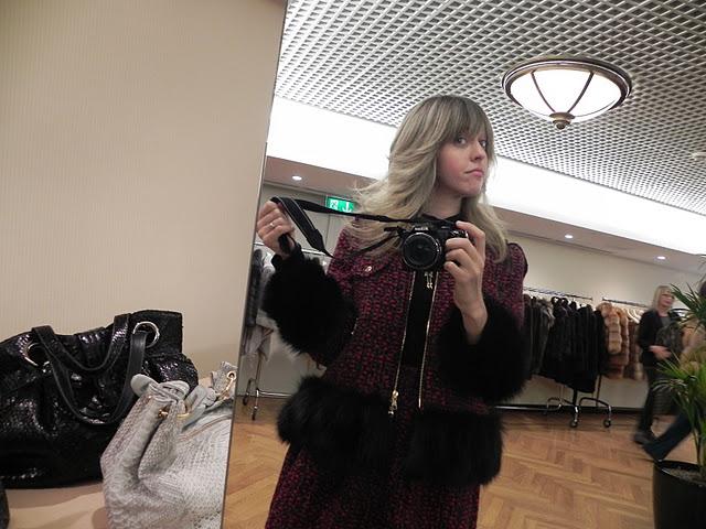 Lady fur taking a selfie in fur shop